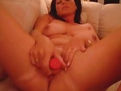 Chubby older woman gets her bald box filled with large sex toy and rubs this giant toy against her clit.